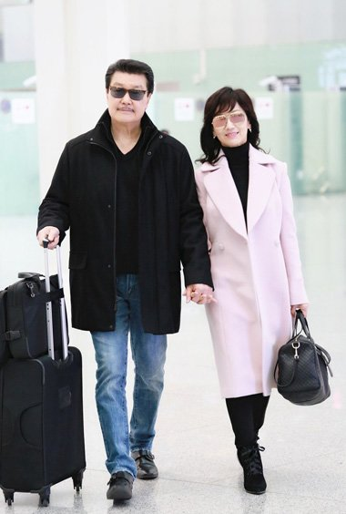 赵雅芝与老公机场甜蜜牵手 中长卷发打造出时尚潮流范