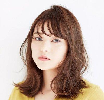 直发刘海发尾部分做偏向一侧的弯曲,棕黄色渲染的中长发两侧有着轻盈图片